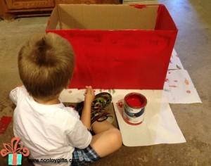 Ребенок красит картонную коробку
